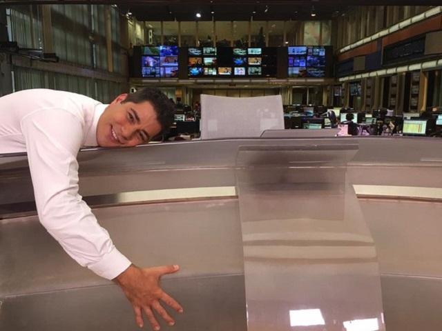 Evaristo Costa posa deitado na bancada do Jornal Hoje: